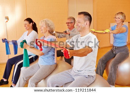 Reha sports for group of happy seniors in fitness center - stock photo