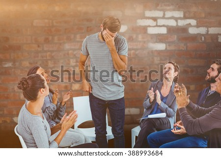 Rehab group applauding delighted man standing up against brick wall - stock photo