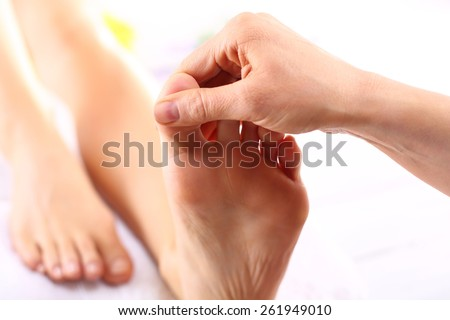 Rehabilitation foot massage. Masseuse massaging woman's foot. - stock photo