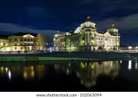 reichstag (bundestag) with reflection in spree river in berlin, germany at night - stock photo