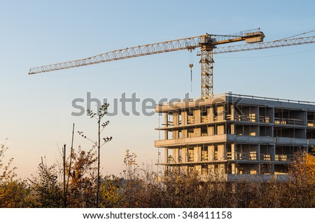 reinforced concrete construction and crane on the residential building construction site - stock photo