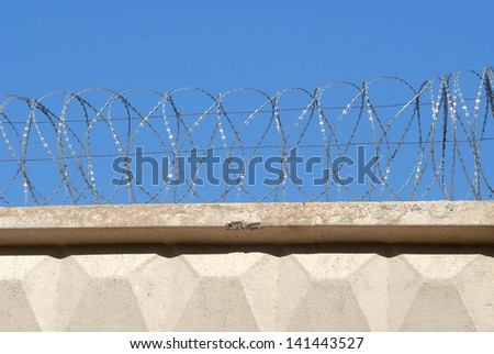 Reinforced concrete fence with barbed wire against the sky