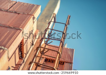 reinforcement steel bars on pillars and layers of bricks on new house construction - details of building structure on construction site - stock photo