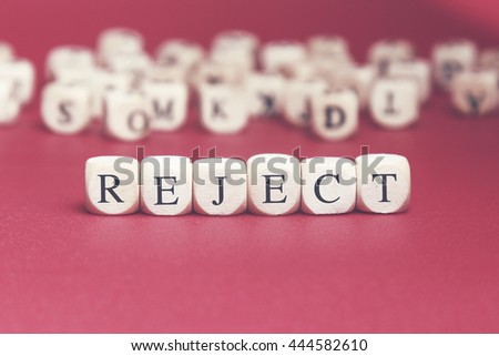 Reject word written on wood cube with red background