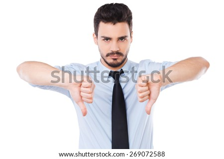 Rejected! Confident young man in shirt and tie looking at camera and showing his thumbs down while standing against white background - stock photo