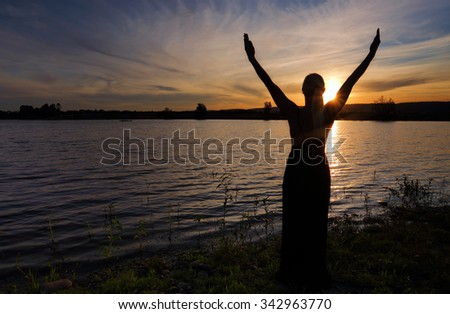 Rejoice Life, Praise, Vitality - A woman with arms outstretched silhouetted against a sunset sky - stock photo
