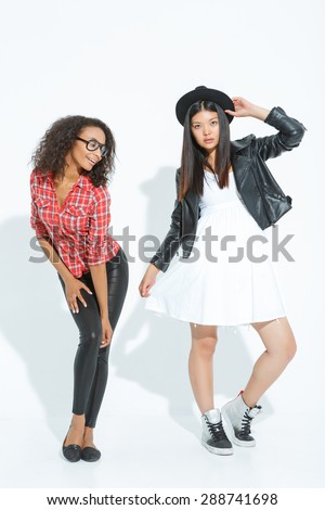 Rejoicing in posing. Pretty girl touching her hat while other lady standing beside and leaning ahead. - stock photo