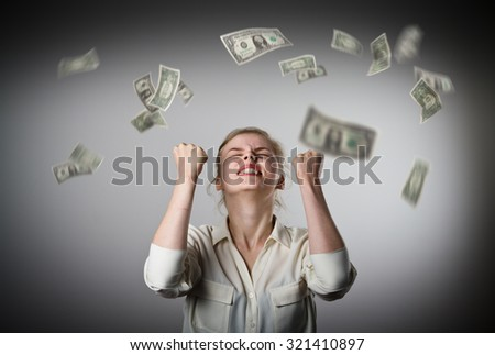 Rejoicing. Young slim woman and falling dollar banknotes. Success, currency and lottery concept.