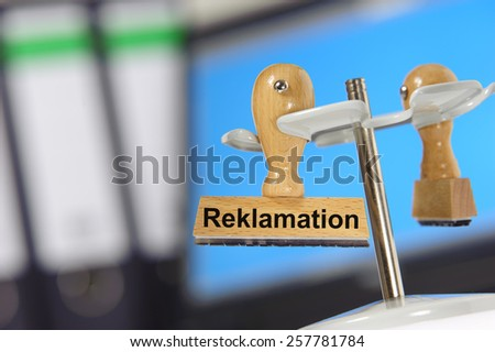 Reklamation printed on rubber rubber stamp in german language - complaint - stock photo
