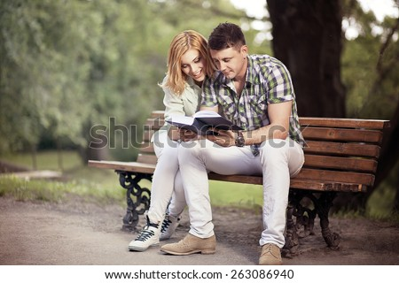 Relationship and education concept. Young happy couple of students are sitting on thebench in the park, learning and smiling. - stock photo