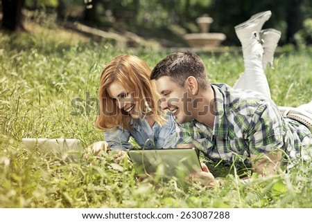 Relationship and education concept. Young smiling couple of students liying on the grass, learning and smiling. - stock photo