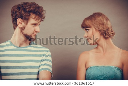 Relationship concept. Woman and man sitting on couch looking serious to each other face to face