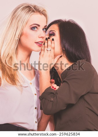 Relationship gossip. Two women multiethnic whispering secret surprised face expression, studio shot
