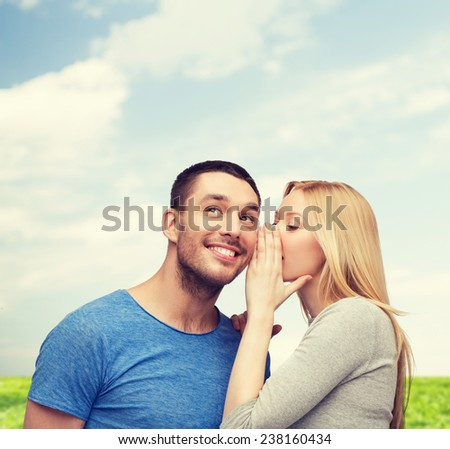 relationships, love and couple concept - smiling girlfriend telling boyfriend secret - stock photo