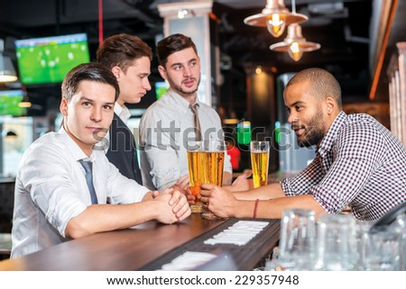 Relax after work. Four friends drinking beer and having fun together in the bar - stock photo