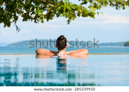 Relax and spa concept. Woman with a flower in hair relaxing in a pool towards the sea  at Krabi, Thailand. - stock photo
