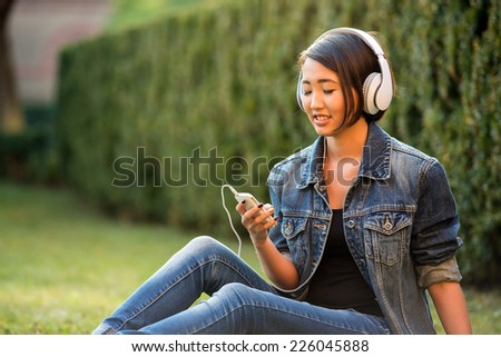 Relax. Beautiful smiling asian female student is sitting on the grass near the college and listening music. - stock photo