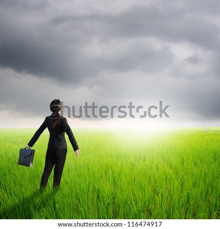 Relax business woman holding bag in green rice field and rainclouds