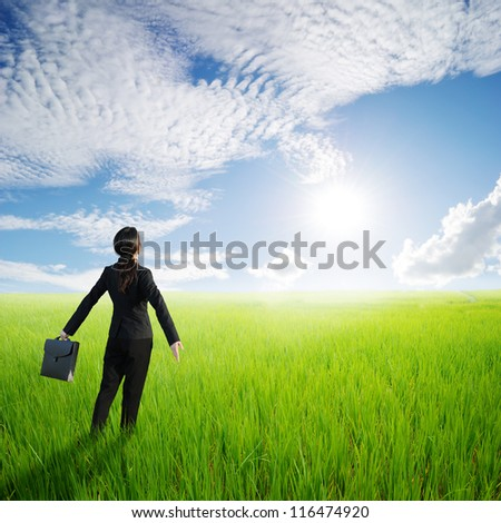 Relax business woman holding bag in green rice field and sun sky