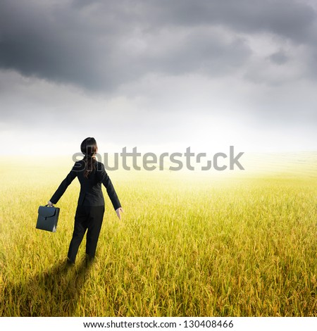 Relax business woman holding bag in yellow rice field and rainclouds