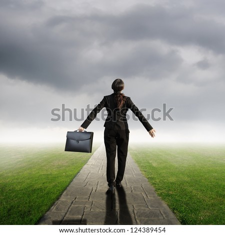 Relax business woman holding bag on Concrete road in Grass fields and rainclouds