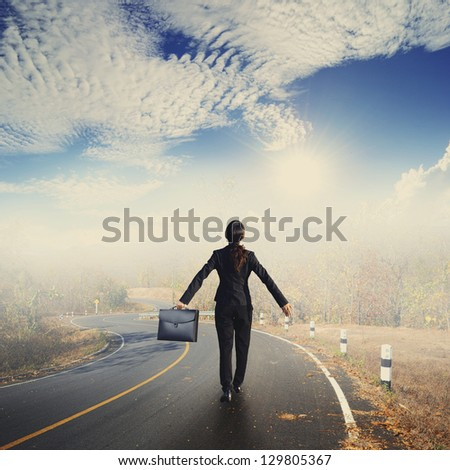 Relax business woman holding bag on Country road and Sun sky