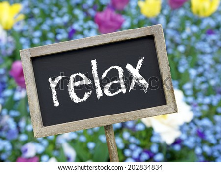 Relax chalkboard on flower background - stock photo