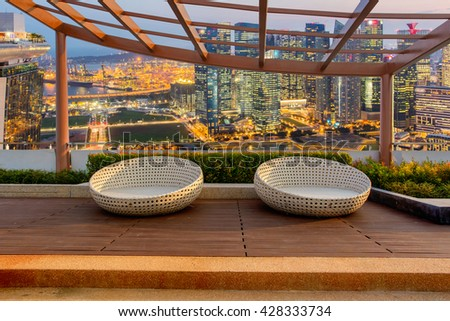 Relax corner on condominium rooftop garden with chairs on Landscape of the Singapore financial district and business building background, Landmark concept - stock photo