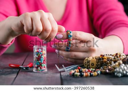 Relax hobby. Female make craft beads - stock photo