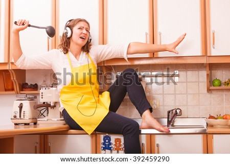 Relax in kitchen. Listening music singing and dancing. Funny happy housewife cook chef with earphones wearing yellow apron sitting and relaxing at home. - stock photo
