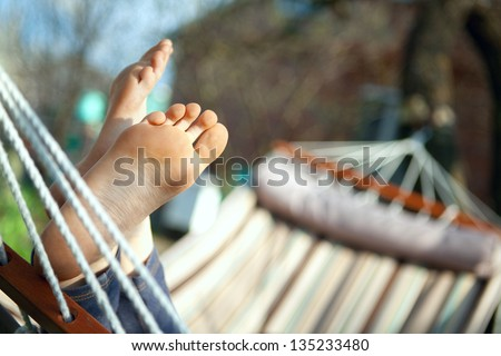 Relax in nature. Feet close up in a hammock - stock photo