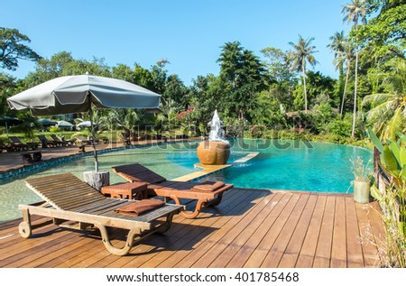 Relax in The Luxury Hotel on The Island of Thailand. Couple of Wooden Chair on Terrace under The Umbrella by The Beautiful Luxury Swimming Pool surrounded by Various Type of Palm Trees in The Garden. - stock photo