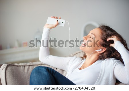 Relax in the rhythm of my music. Attractive young woman lwith earphones and smartphone sitting on sofa at home. - stock photo
