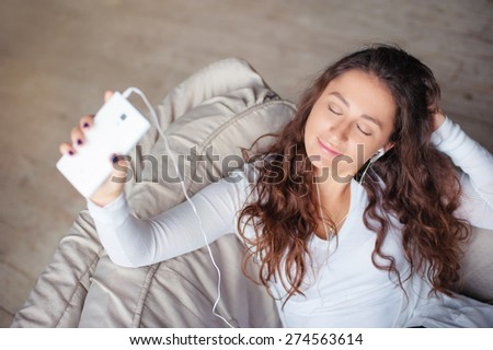 Relax in the rhythm of my music. Attractive young woman with earphones and smartphone sitting on sofa at home. - stock photo