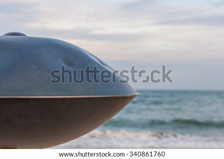 Relax music background. Hands percussion. The Hang or handpan with sea On Background. the hang is a traditional ethnic drum musical instrument. - stock photo