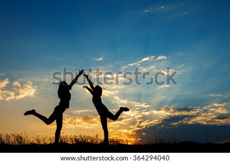 Relax of two women friends standing and sunset silhouette with copy space. - stock photo