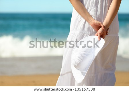 Relax on summer holidays concept. Woman on beach vacation relaxing and holding white hat. Copy space blue sea background. - stock photo