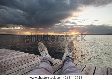 relax on the lake - man on the pier at sunset - stock photo