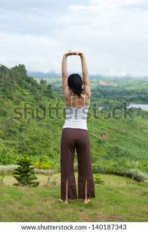 Relax time Asian yoga girl standing in front of the green hill in the morning
