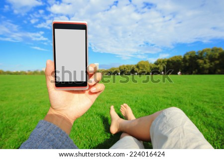 Relax using smart phone and barefoot enjoy nature in the green lawn