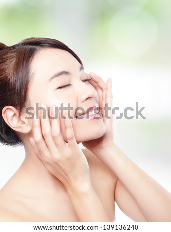 Relax woman closed eyes and finger point to eyes, concept for eye and skin care, isolated over nature green background, asian beauty - stock photo