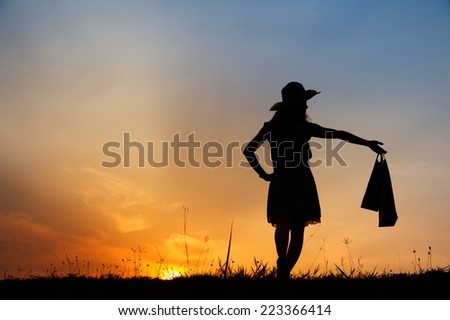 Relax Woman holding shopping bags in sunset silhouette - stock photo