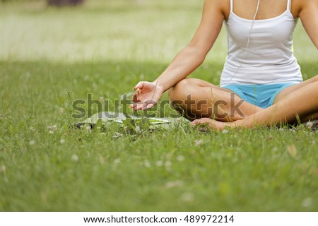 Relax woman in lotos pose on grass.