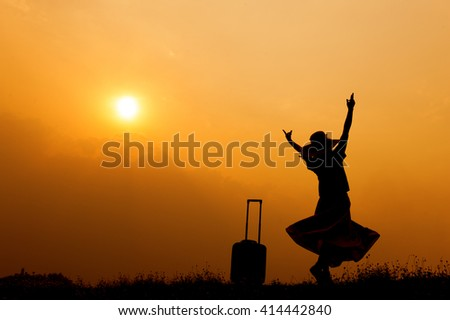 Relax woman with a suitcase on a meadow  at sunset silhouette.Holiday summer travel concept - stock photo