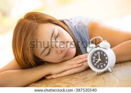 Relax women take a break and sleeping with classic alarm clock on wood table in park