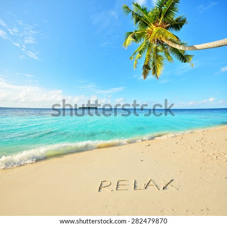 Relax word written on the tropical beach -- Tropical beach vacation and travel concept   - stock photo