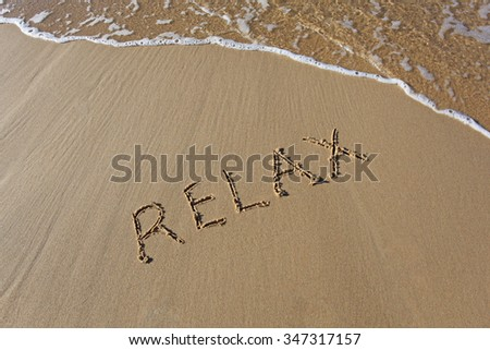 Relax written in the sand at the beach with wave rolling up