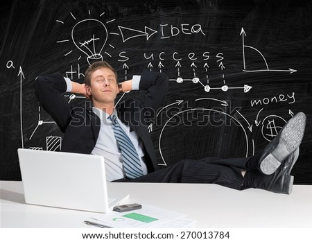 Relaxation. Business man or office worker daydreaming with feet on table - stock photo