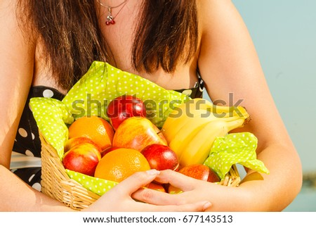 Relaxation during summertime concept. Woman holding picnic basket with fruits. Water sea in background.