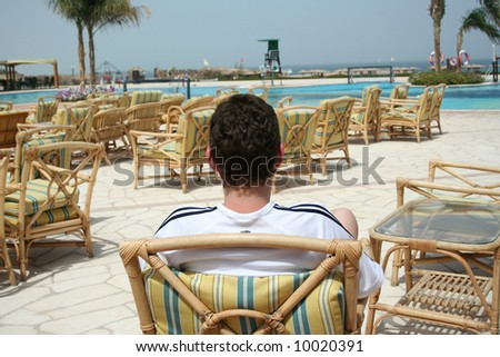 Relaxation in an armchair near pool